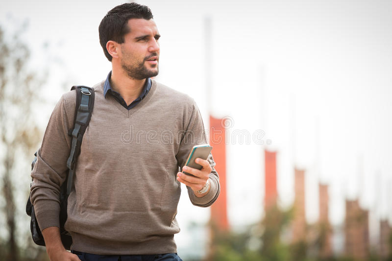 För brukssmartphone för ung man stads- stad royaltyfri bild
