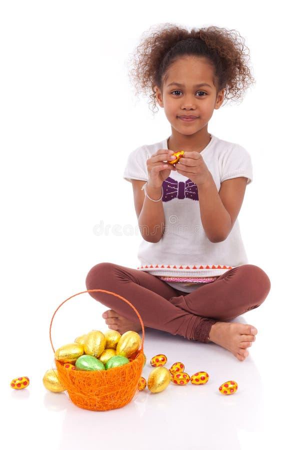 För chokladester för afrikansk asiatisk flicka hållande ägg royaltyfri bild