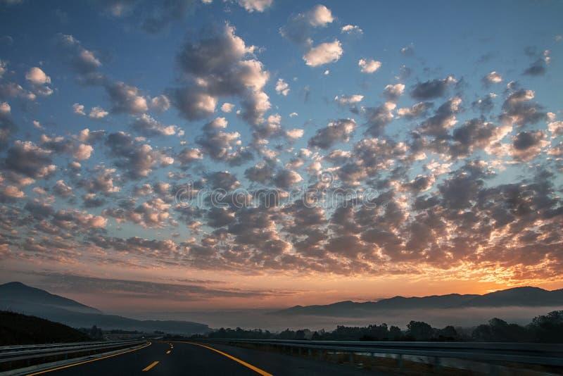 För Clouds Street Highway för soluppgångsolnedgångherde för Europa sol dimma för berg himmel arkivbild