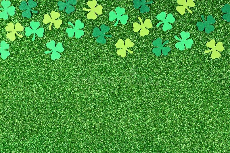 För dagöverkant för St Patricks gräns av treklöverer över glittery grön bakgrund royaltyfri fotografi
