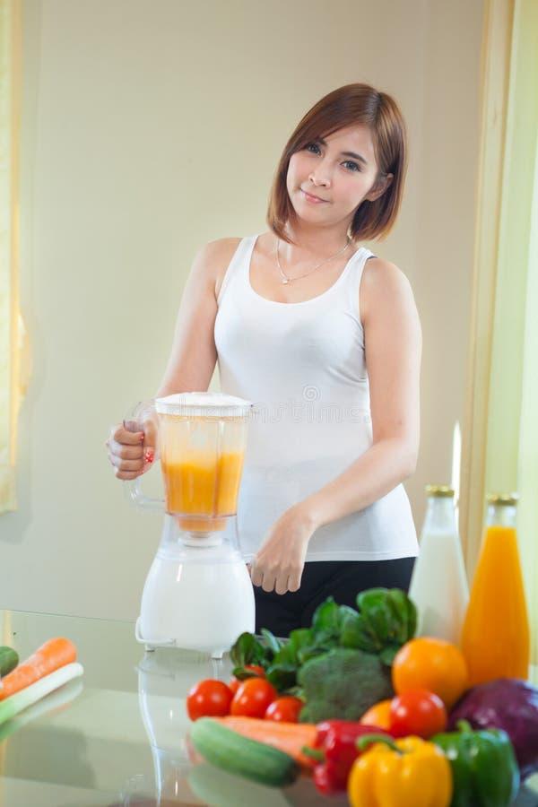 För danandefrukt för ung kvinna Smoothie i blandare royaltyfria foton