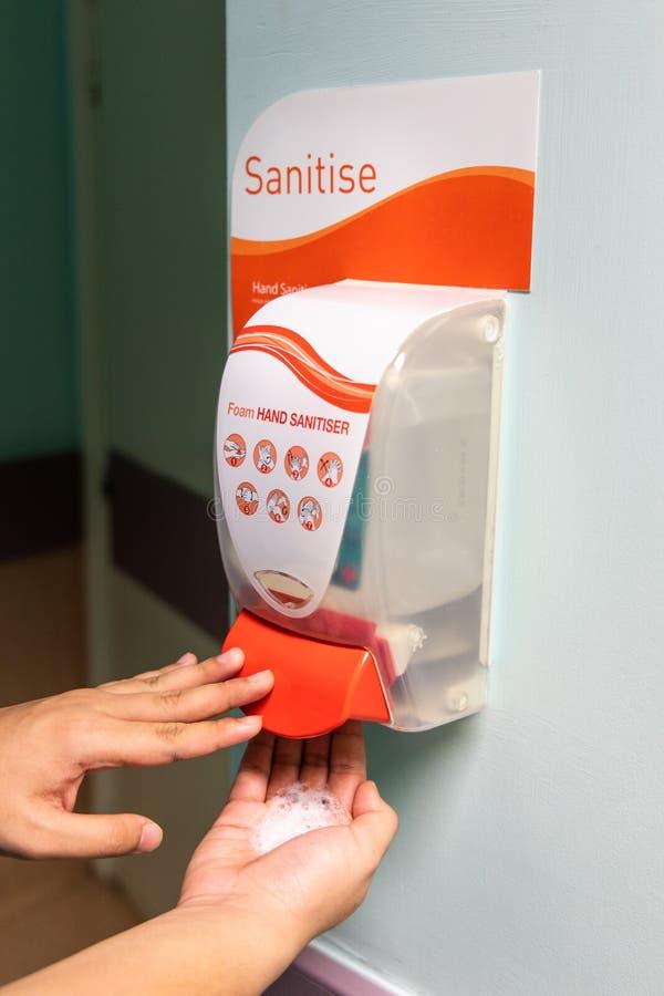 För desinfektionsmedelsanitizer för person fördelande flytande på handen på baren royaltyfri foto