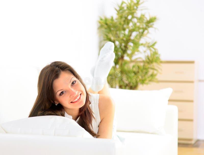 för divan le för flicka ner liggande royaltyfria bilder