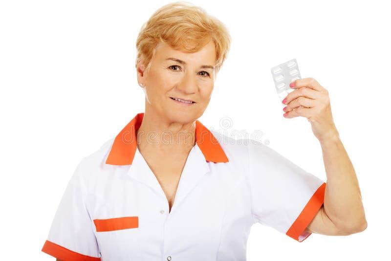 För doktors- eller sjuksköterskahåll för leende äldre kvinnlig blåsa av preventivpillerar royaltyfri foto