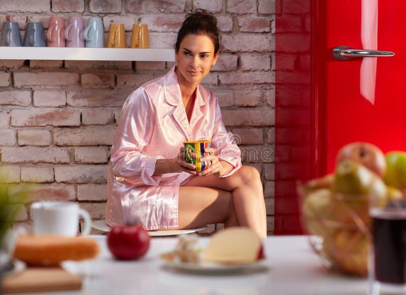 För drinkfrukost för ung kvinna kaffe i pyjama royaltyfri fotografi