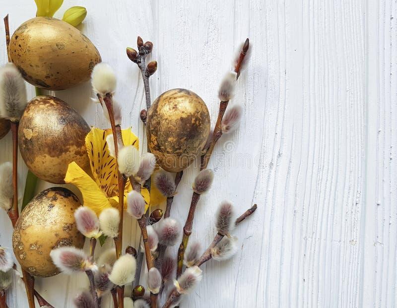 För easter för vaktelägg pil filial på en vit träbakgrund, blommaalstroemeria arkivbilder