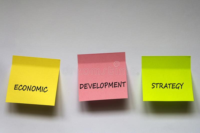 ` För `-ekonomisk utvecklingstrategi, uttrycket är skriftlig på mång--färgade klistermärkear på vit bakgrund royaltyfria foton
