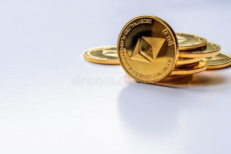 För Ethereum för guld- faktiska pengar som mynt crypto valuta staplas på ljus bakgrund royaltyfria foton