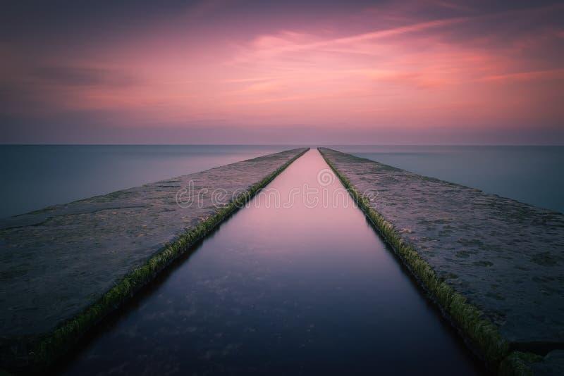 För exponeringssolnedgång för bred vinkel lång sikt av havet från en pir royaltyfri fotografi