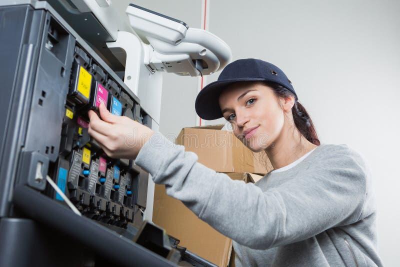 För färgpulverkassetter för kvinnlig tekniker ändrande fotokopiator royaltyfri foto