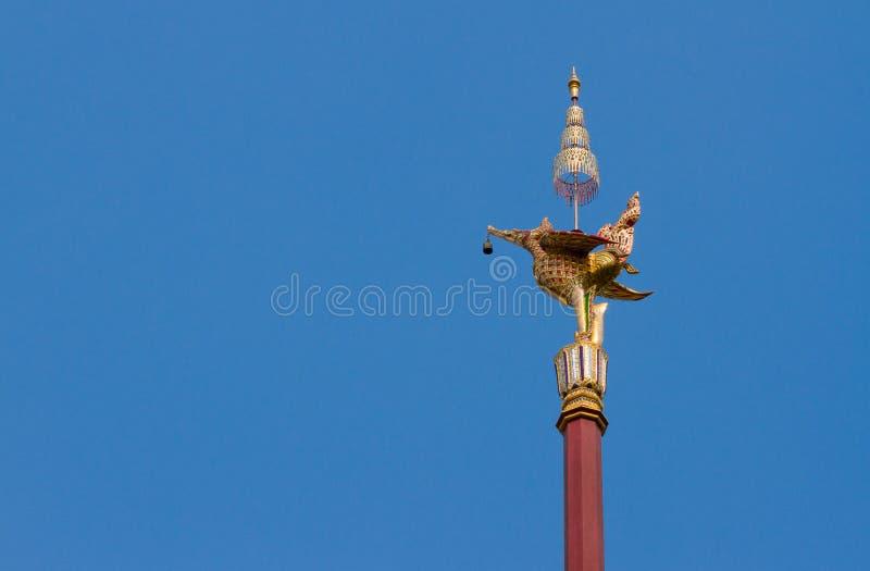 För fågellampa för thailändsk stil guld- staty och blå himmel arkivfoton