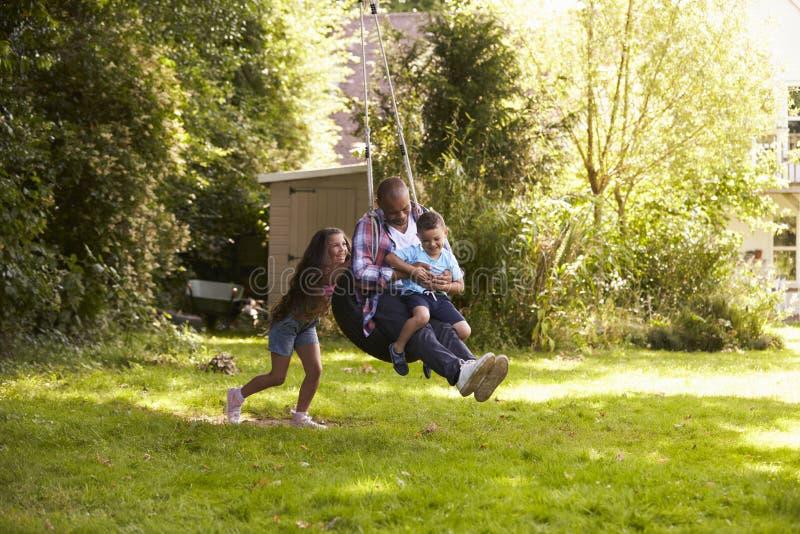 För faderAnd Son On för dotter driftig gunga gummihjul i trädgård arkivbilder