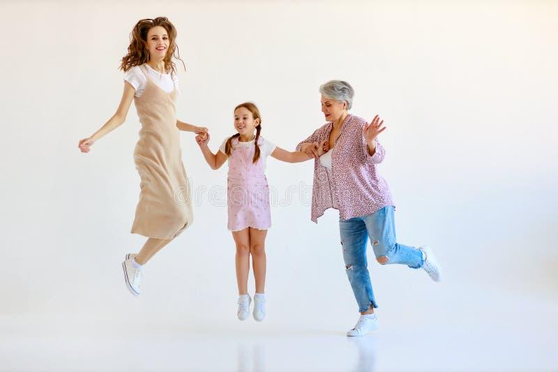 För familj som tre dans för utvecklingar farmor, moder- och barnhoppar på vit bakgrund royaltyfri bild