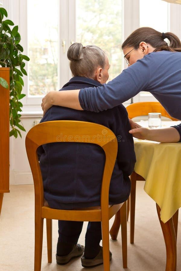 För farmorsondotter för gammal kvinna omfamning arkivfoto