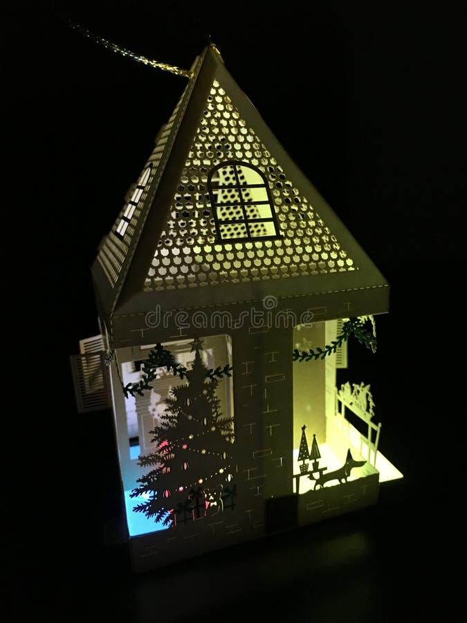 För ferielaser för Lit övre garnering för hus för papper för snitt med en julgran och färgrika glade ljus som glöder i mörkret royaltyfri foto
