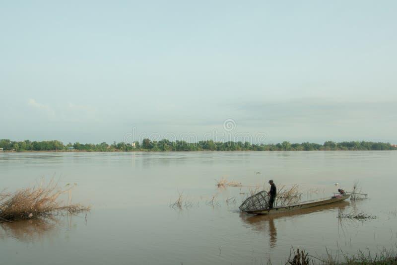 För fiskare bärgningfisk mot efterkrav i floden arkivfoton