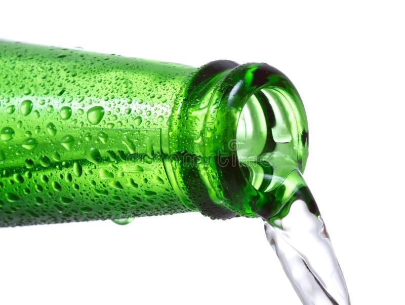 för flaska grönt hällande vatten ner arkivfoton