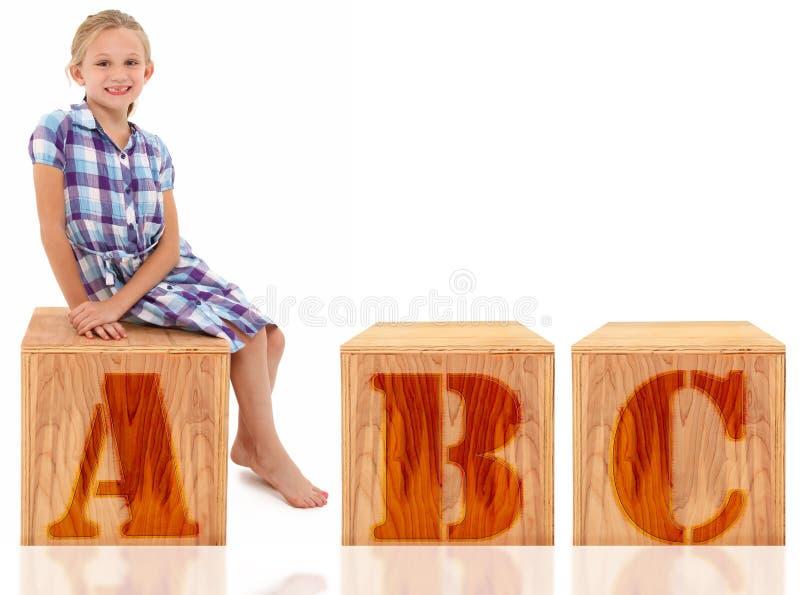 för flickabokstav för b c sitting royaltyfria foton
