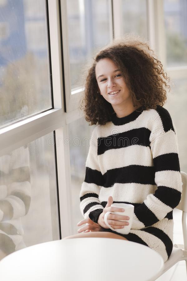 För flickadriks för lockigt hår tonårigt te hemma fotografering för bildbyråer