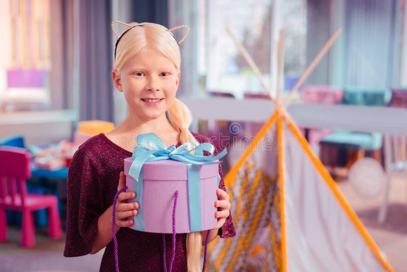 För flickainnehav för realitet förtjust blond ask med gåva royaltyfri foto