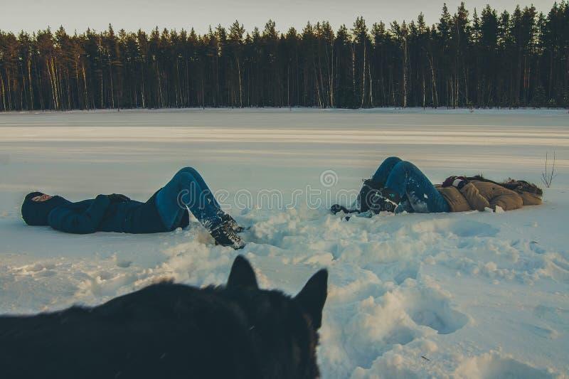 För flickor som ligger i den hållande ögonen på hunden för snö fotografering för bildbyråer