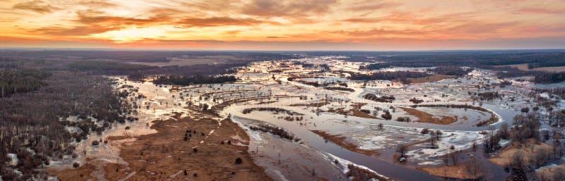För flodflod för vår smältande panorama Solnedgång över ängar royaltyfri bild