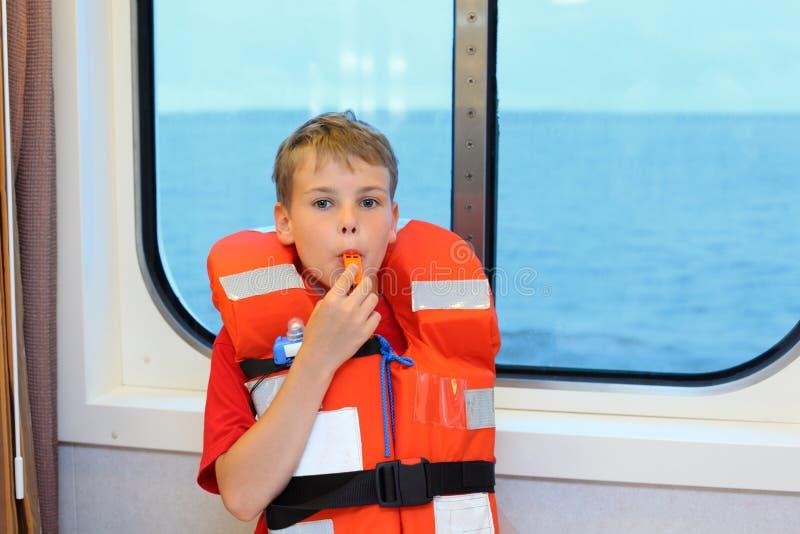 För flytvästblows för pojke iklädd vissling