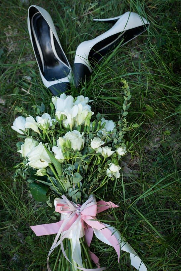 för fokusförgrund för 3 bukett bröllop Kvinnliga skor för modebeiga- och svartbröllop med buketten för brud` s av vita rosor och  arkivfoton