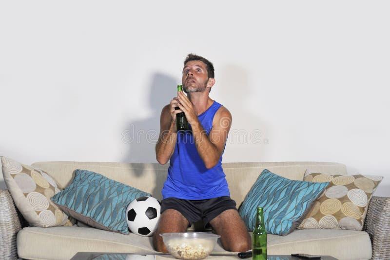 För fotbolllek för ung attraktiv man hållande ögonen på TV be nervöst a royaltyfri fotografi
