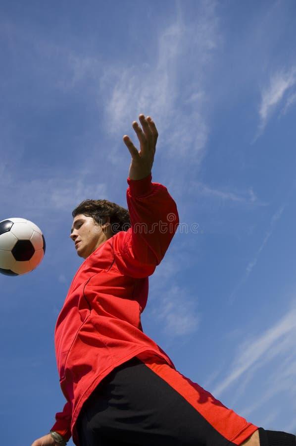 för fotbollsspelarered för boll kontrollerande fotboll arkivbild