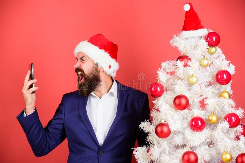 För framsidakläder för man skäggig dräkt och telefon för santa hatthåll Cellnätverksöverbelastning Grabb som förargas av kvalitet royaltyfria foton