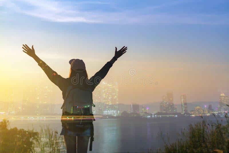 För frihetshandelsresande för dubbel exponering anseende för kvinna med lyftta armar och tycka om en härlig natur och hurra ryggs arkivbild
