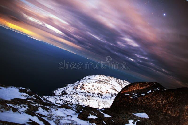 För frostigt djupblått arktiskt hav nattlandskap för solnedgång Nordliga kalla vinternaturklippor och moln, svart stenig kust royaltyfri bild