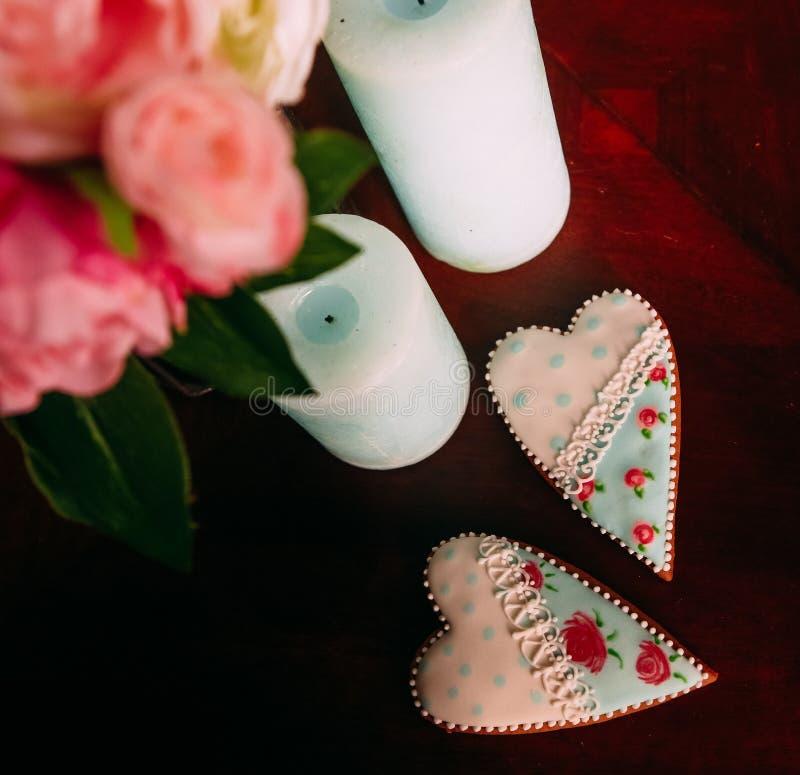 För gåvapepparkaka för två hjärtor träbakgrund med stearinljusblomman arkivbilder