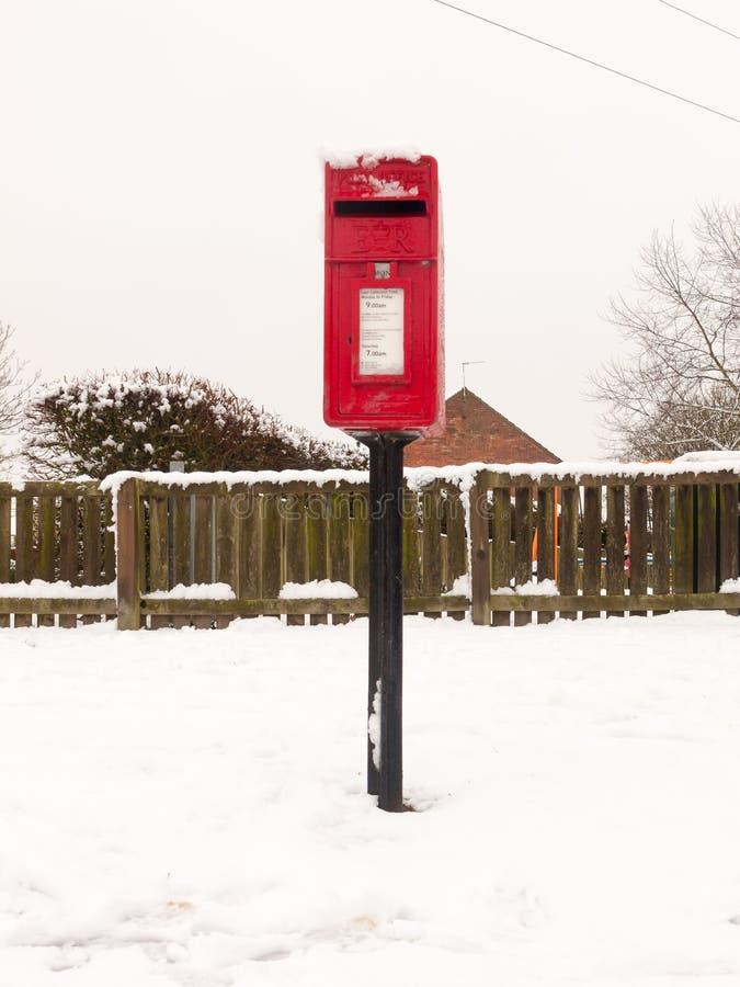 by för gata för röd bystolpeask utvändig med snövinter royaltyfri bild