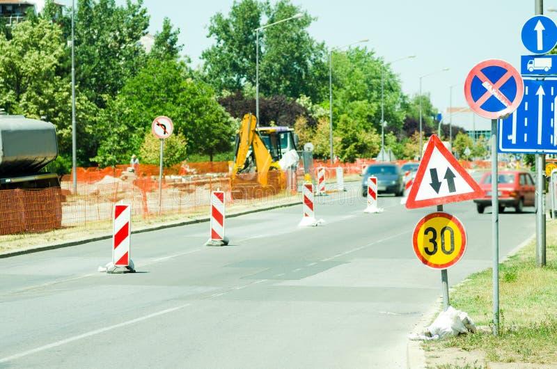 För gatarekonstruktion för arbete framåt plats med tecknet och staket som vägbarrikaden royaltyfria foton