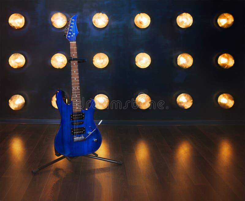 för gitarrillustration för begrepp elektrisk musik Anseende för elektrisk gitarr på trägolvet nära arkivfoton