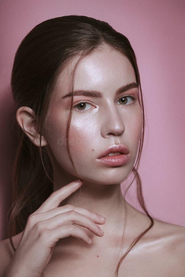 För glamourkvinna för skönhet som långt hår för försiktig brunett för stående samlas med näck stil på rosa bakgrund arkivbilder