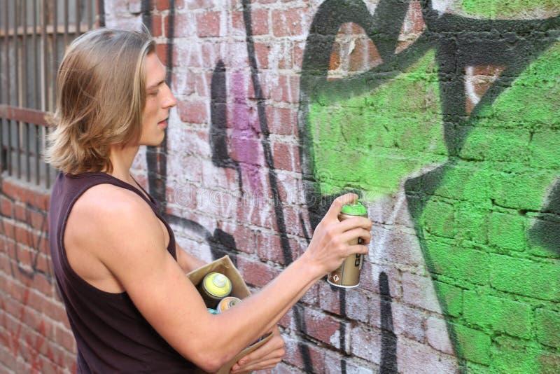 För gräsplansvart för ung man målarfärg på en grafittivägg Rum för text royaltyfria bilder