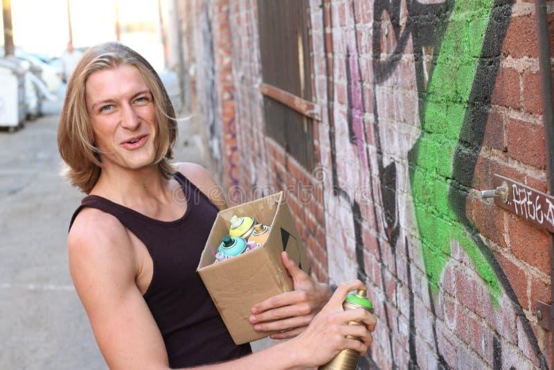För gräsplansvart för ung man målarfärg på en grafittivägg Rum för text fotografering för bildbyråer