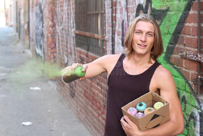 För gräsplansvart för ung man målarfärg på en grafittivägg Rum för text arkivbild