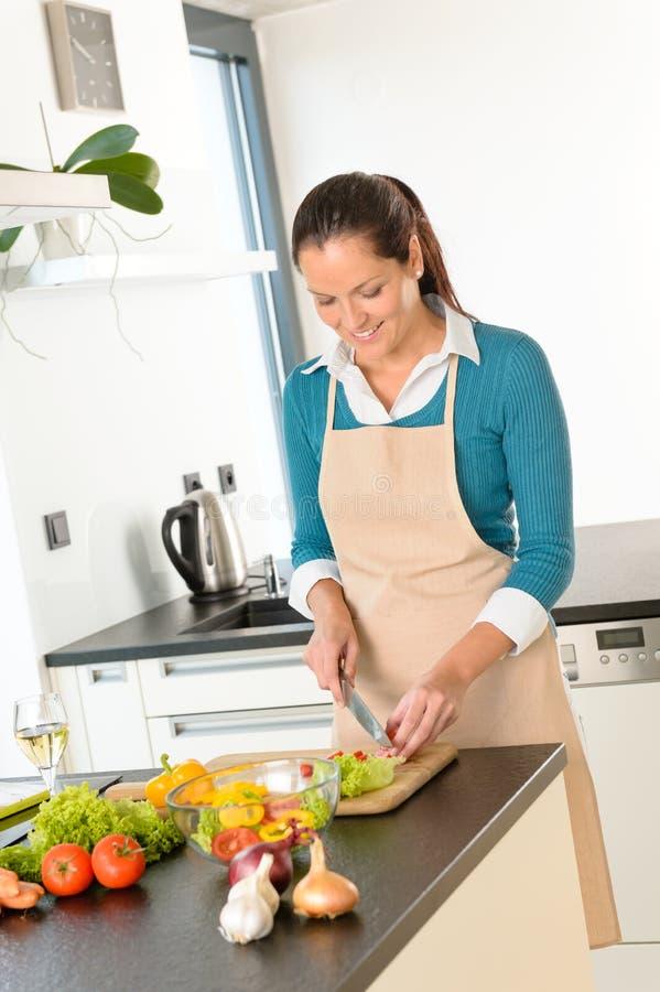 För grönsakkök för kvinna som bita stå är lyckligt royaltyfria bilder