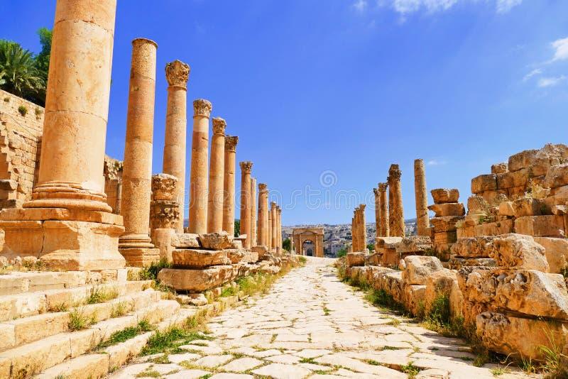 För Greco-romare för scenisk sikt forntida kolonner Corinthian på Colonnaded Cardo till den norr Tetrapylonen i Jerash, Jordanien royaltyfria bilder