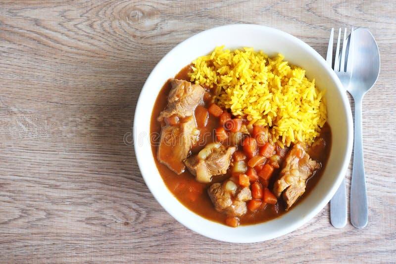 för grisköttfransyska för japansk stil curry med gula curryris i den vita bunken på trätabellen royaltyfri fotografi