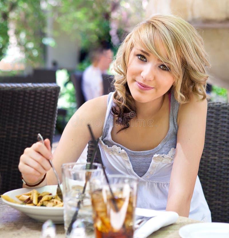 för gullig utomhus- pasta ätaflicka för cafe royaltyfria foton