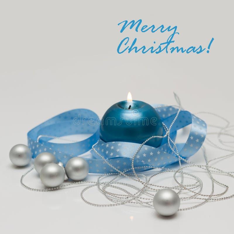 För hälsningkort för glad jul som mall göras av blåttstearinljuset med strumpebandsorden, silverjulbollar och silverrad av pärlor fotografering för bildbyråer