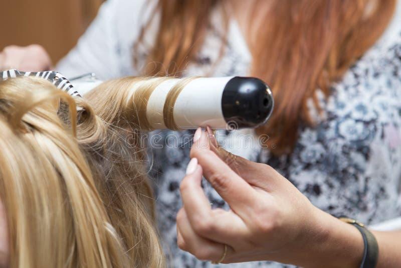 För hårfrisör för brunett som röd konstnär gör den lockiga frisyren till b royaltyfri fotografi