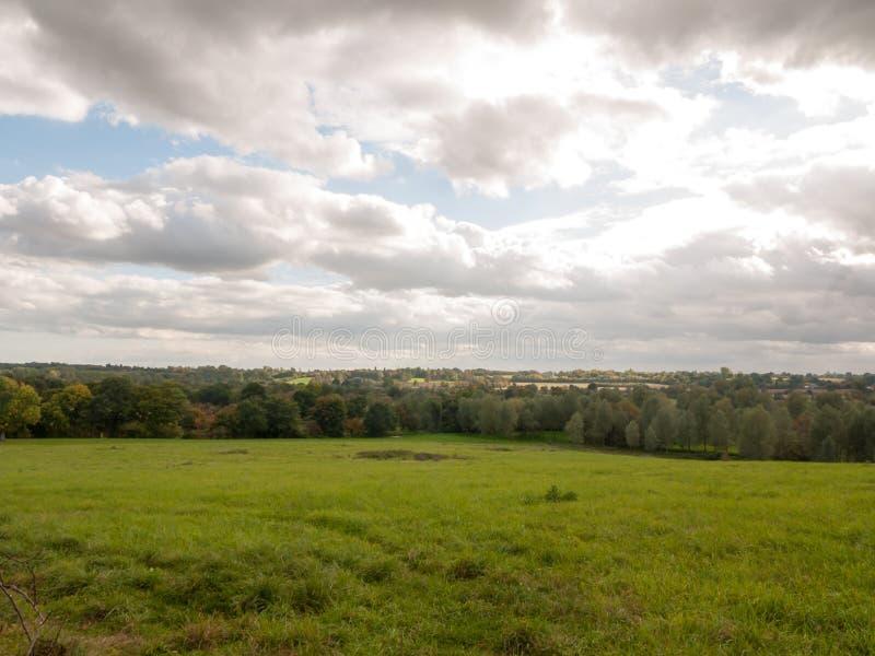 För höstdag för stormiga moln mulet solljus över öppet fält med royaltyfri fotografi
