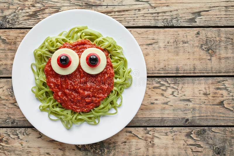 För halloween för grön spagettipasta fejkar det idérika monstret mat med blodtomatsås royaltyfri foto