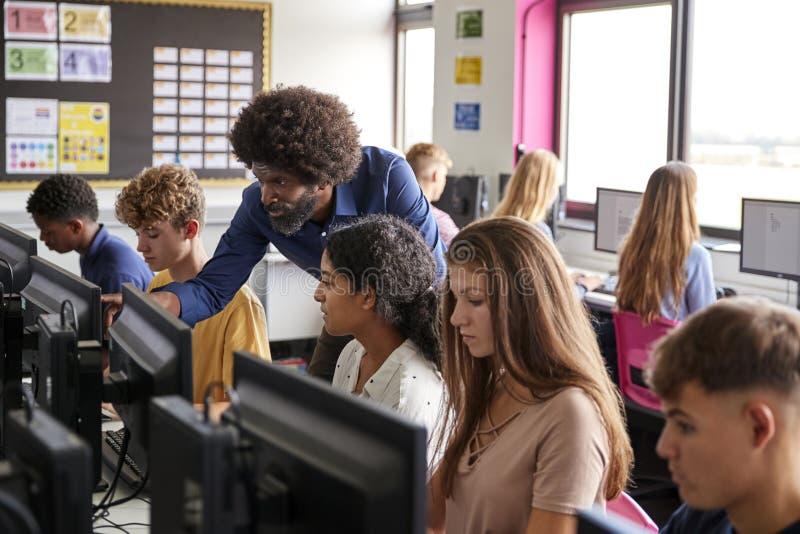 För Helping Teenage Female för manlig lärare Working In Computer för student högstadium grupp royaltyfri fotografi